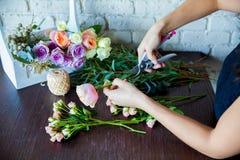 Kwiaciarnia przy pracą. Kobieta robi wiośnie kwiecistym dekoracjom Zdjęcia Royalty Free