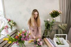 Kwiaciarnia w warsztacie pakuje bukiet Zdjęcia Royalty Free