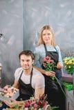 Kwiatów asystenci jest ubranym czarnych fartuchy zdjęcia stock
