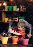 Kwiat opieki podlewanie Glebowi u?y?niacze Ojciec i syn Ojca dzie? brodata m??czyzny i ch?opiec mi?o?ci natura Rodzinny dzie? zdjęcia royalty free