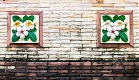 Kwiat statuy na ściana z cegieł. Fotografia Stock