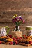 Kwiat waza, ceramiczni naczynia z asortowaną mieszanką dzikie owoc i ciastka, zdjęcie stock