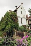 Kwiatu łóżko piękni kwiaty i stary dom z kominem Fotografia Stock