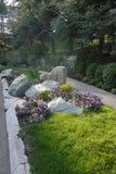 Kwiatu łóżko z kamieniami i błękitną petunią wzdłuż zwyczajnego przejścia w parku zdjęcie royalty free