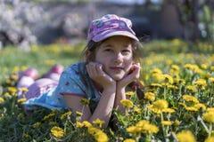 kwiatu dziewczyny trawy mały lying on the beach plenerowy Uśmiechnięty dziewczyny lying on the beach na polu z dandelions Obraz Stock