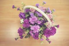 Kwiatu kosz na drewnianym odgórnym widoku Zdjęcia Royalty Free