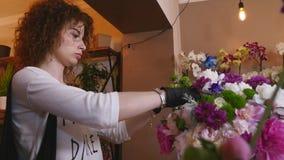 Kwiatu sklep, kwiaciarnia Układa Nowożytnego bukiet, młode przystojne kwiaciarnie pracuje przy kwiatu sklepem robi bukietowi zbiory