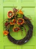 Kwiatu wianek na jaskrawym - zielony drzwi obrazy stock
