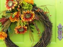 Kwiatu wianek na jaskrawym - zielony drzwi obraz royalty free