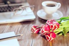 Kwiaty na drewno stole filiżanka kawy i laptop na tle Obraz Stock