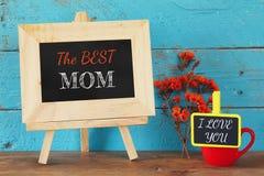 Kwiaty obok blackboard z zwrotem: NAJLEPSZY mama i mały blackboard z zwrotem: Kocham CIEBIE głębii pola płycizny stół drewniany Obraz Royalty Free