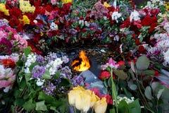 Kwiaty przynoszący ludźmi płonącego ` Wiecznie Pożarniczy ` na zwycięstwo dniu nad fascism, Maj 9 obraz stock