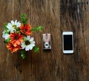 Kwiaty w wazie, kamerze i telefonie na starym drewno stole, Obrazy Royalty Free