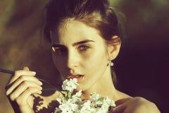 Kwiaty z kruszcowym rozwidleniem, kobieta je czereśniowego okwitnięcia płatki fotografia stock