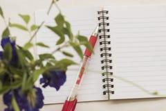 Kwiaty z notatnikiem na stołowym bielu Fotografia Stock