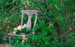 Kwiaty zasadzający w siedzeniu antykwarski krzesło Obraz Stock