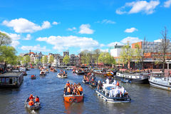 KWIECIEŃ 27: Amsterdam kanały pełno łodzie i ludzie w pomarańcze du Obrazy Royalty Free