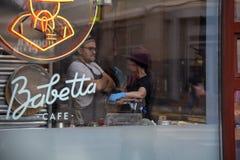 Kwiecień 2019, Babett kawiarnia, Moskwa, Rosja Fotografia brać przez cukiernianego okno Dziewczyna w błękitnym kapeluszu i rękawi fotografia royalty free