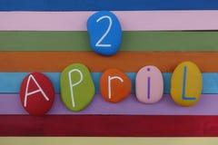 2 Kwiecień, komponujący z barwionymi kamieniami nad wielo- barwioną drewnianą deską ilustracja wektor