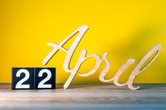 Kwiecień 22nd Dzień 22 miesiąc, kalendarz na drewnianym stole i koloru żółtego tło, Wiosna czas, opróżnia przestrzeń dla teksta Fotografia Stock