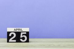 Kwiecień 25th Dzień 25 miesiąc, kalendarz na drewnianym stole i purpury tło, Wiosna czas, opróżnia przestrzeń dla teksta Obraz Stock