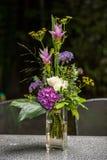 Kwiecista dekoracja w wazie z wodą na stole fotografia stock