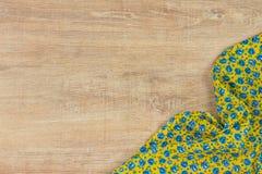 Kwiecista deseniowa sukienna pielucha na pustym drewnianym tle Zdjęcie Stock