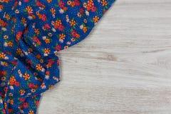 Kwiecista deseniowa sukienna pielucha na pustym drewnianym tle Fotografia Stock