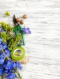 Kwiecisty tło - kwiaty i kwiaciarni narzędzia na drewnianym tle zdjęcia stock
