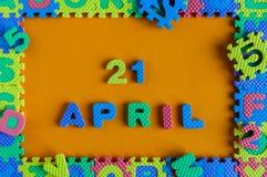 Kwietnia 21st dzień 21 miesiąc, dzienny kalendarz dziecko zabawki łamigłówka na pomarańczowym tle Wiosna czasu temat Fotografia Royalty Free