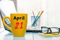 Kwietnia 21st dzień 21 miesiąc, kalendarz na ranek filiżance, biznesowego biura tło, miejsce pracy z laptopem i Obrazy Stock