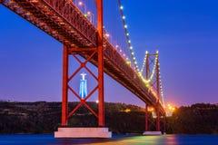 Kwietnia 25th Chrystus i most królewiątko statua w Lisbon Portugalia przy zmierzchem Fotografia Royalty Free