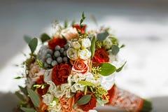 Kwitnie ślubnego bukiet z złocistymi obrączkami ślubnymi panny młode zdjęcia stock