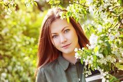 Kwitnie jabłoń w wiośnie i wiśnia Młoda szczęśliwa kobieta z niebieskimi oczami iść w jabłoni obraz stock