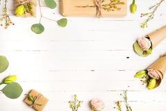 Kwitnie skład Kwiaty i prezenty na białym tle Mieszkanie nieatutowy, odgórny widok obrazy stock