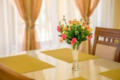 Kwitnie w wazie na stołowym i nadokiennym parapetu tle Rocznika styl dekoruje zdjęcie stock