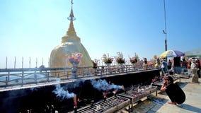 Golden Rock Shrine, Kyaiktiyo, Myanmar. Kyaiktiyo, Myanmar - February 16, 2018: the altar of Golden Rock Shrine with fuming incense sticks, burning candles and stock video footage