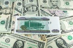Kyats de Myanmar en fondo de muchos dólares Imagen de archivo
