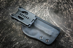Kydex holster for pistol. Handmade kydex holster for pistol on a grungy wood table Stock Photo