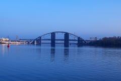 "KYIV,乌克兰†""2016年11月16日:对未完成的桥梁的早晨视图 城市克里姆林宫横向晚上被反射的河 Podolsko-Voskresenskij桥梁 库存图片"