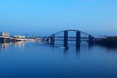 "KYIV,乌克兰†""2016年11月16日:对未完成的桥梁的早晨视图 城市克里姆林宫横向晚上被反射的河 汽船在Dnieper漂浮 库存照片"