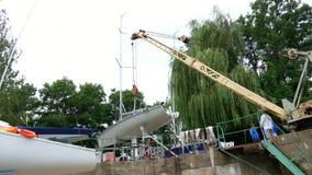 KYIV,乌克兰, YACHTING-JULY 29日2018年:在第聂伯河岸,在码头,一台卷扬的起重机培养一条白色游艇 放置 股票录像