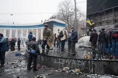 KYIV,乌克兰:暴乱的活动家在制服的等待与警察的战斗在被烧的正方形 图库摄影