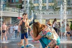 KYIV,乌克兰2017年8月13日:愉快的孩子获得使用的乐趣在城市给水喷泉在热的夏日 库存照片