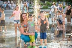 KYIV,乌克兰2017年8月13日:愉快的孩子获得使用的乐趣在城市给水喷泉在热的夏日 免版税库存照片