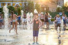 KYIV,乌克兰2017年8月13日:愉快的孩子获得使用的乐趣在城市给水喷泉在热的夏日 免版税库存图片