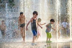 KYIV,乌克兰2017年8月13日:愉快的孩子获得使用的乐趣在城市给水喷泉在热的夏日 库存图片