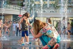 KYIV,乌克兰2017年8月13日:愉快的孩子获得使用的乐趣在城市给水喷泉在热的夏日 免版税图库摄影
