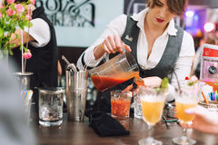 Kyiv,乌克兰- 2016年10月30日, :男服务员节日 年轻俏丽的妇女侍酒者做鸡尾酒 库存照片
