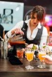 Kyiv,乌克兰- 2016年10月30日, :男服务员节日 年轻俏丽的妇女侍酒者做鸡尾酒 免版税库存图片
